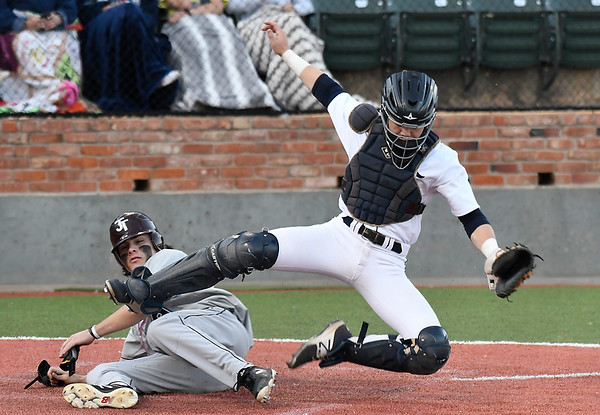 Enid's Hayden priest is konocked off his feet by Jenks' Tanner Lawrence Tuesday April 10, 2018 at David Allen Memorial Ballpark. (Billy Hefton / Enid News & Eagle)