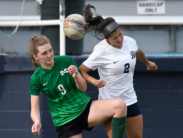 Enid's Dhamar Carrillo heads the ball against Muskogee's Maria Vazquez Friday April 20, 2018 at D. Bruce Selby Stadium. (Billy Hefton / Enid News & Eagle)
