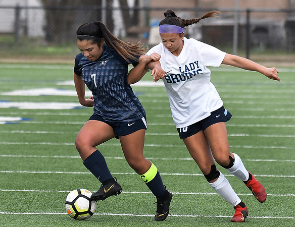 Enid's Janet Moreno tries to pull away from Bartlesville's Peyton Winter Friday April 5, 2019 at D. Bruce Selby Stadium. (Billy Hefton / Enid News & Eagle)