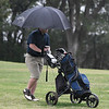 Enid's Traytin Mcdonald protects himself from the weather during the regional tournament Monday April 29, 2019 at Meadowlake Golf Course. (Billy Hefton / Enid News & Eagle)