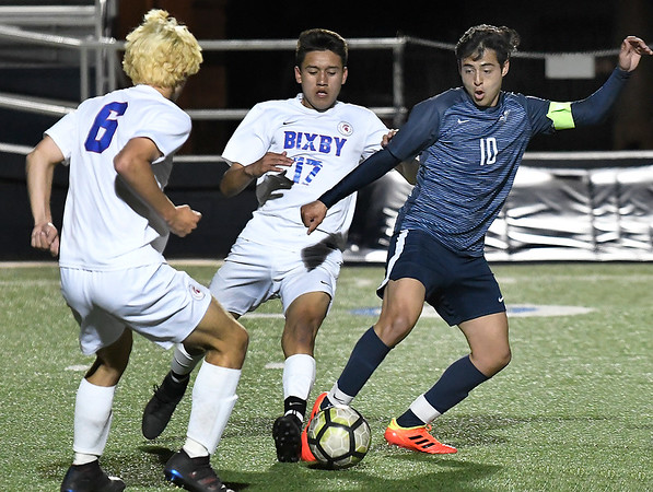 Enid's Ivan Delgadillo tries to maneuver through Bixby's Trevor Holmes and Martin Martinez Friday April 12, 2019 at D. Bruce Selby Stadium. (Billy Hefton / Enid News & Eagle)