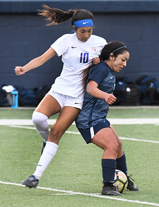 Enid's Janet Moreno tries to hold off Bixby's Giselle Urquiza Friday April 12, 2019 at D. Bruce Selby Stadium. (Billy Hefton / Enid News & Eagle)