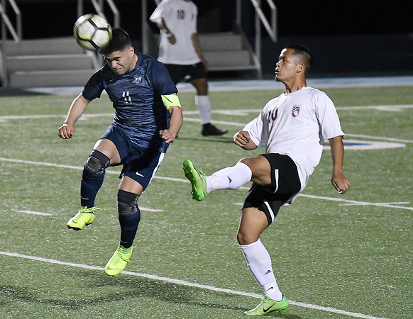 Enid's Marcos Arambula heads the ball away from Jenks' Nang Tung Tuesday April 16, 2019 at D. Bruce Selby Stadium. (Billy Hefton / Enid News & Eagle)