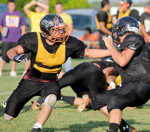 A Canton Tiger (left) tackles Buffalo quarterback, Kyle Hash, behind the line of scrimmage at Jet Friday, August 23, 2013. (Staff Photo by BONNIE VCULEK)