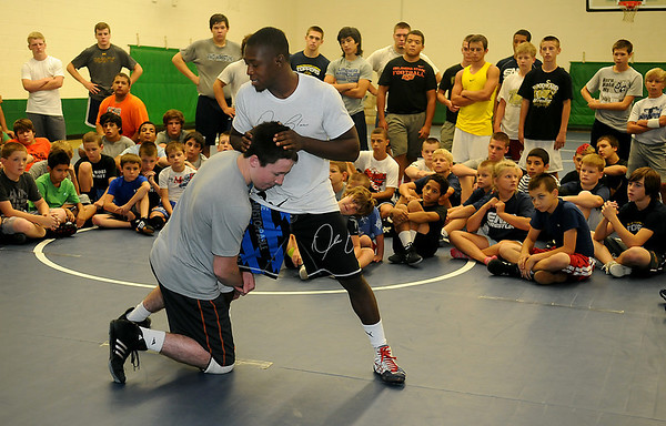 Wrestlers watch as John Morrison and Obe Blanc demonstrate a defensive move during the Enid Camp of Champs at Emerson Middle School Friday, August 2, 2013. Morrison, a senior wrestler at Oklahoma State University, is an NCAA All-American, while Obe Blanc is a 2 x World Wrestling Team member. (Staff Photo by BONNIE VCULEK)