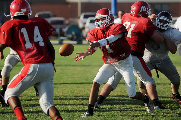 Medford quarterback Alex Koehn tosses the pigskin to running back Ryan Banks during a play against Waynoka at the DCLA scrimmage Friday, August 30, 2013. (Staff Photo by BONNIE VCULEK)