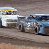 Richard Pece (right) races to the mini-stock victory as Nick Rummell finishes second during opening night at the Enid Speedway Saturday, August 24, 2013. Fan enthusiasts waited in line for over an hour as the large crowd was excited to see racing return to Enid. (Staff Photo by BONNIE VCULEK)