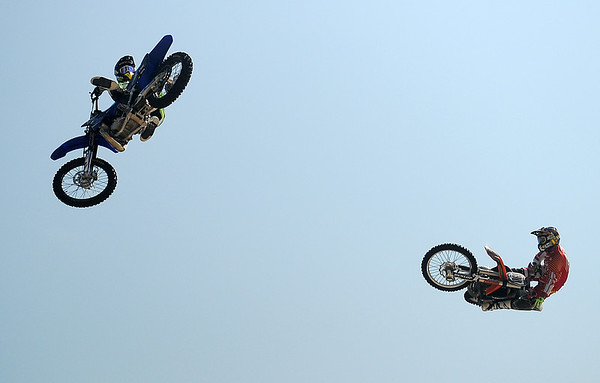 Matt Buyten ((left) and Cowboy Kenny Bartram, both X-Games metalists, perform different freestyle motor cross stunts less than 100 feet apart during the Steel Rodeo Tour at the Greater Oklahoma Sportsman's Outdoor Expo at the Chisholm Trail Expo Center Saturday, August 24, 2013. (Staff Photo by BONNIE VCULEK)