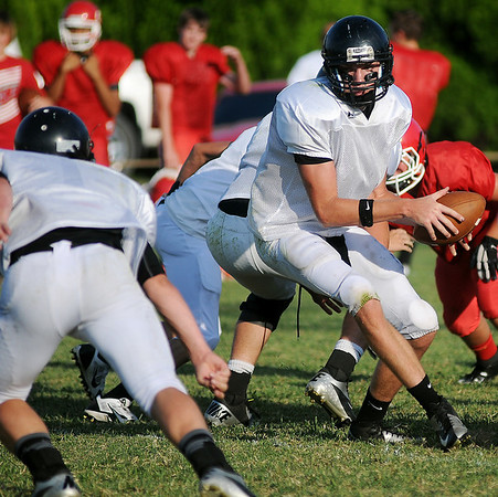 Pond Creek-Hunter's Derrick Holcomb takes the snap and tosses the ball to a running back during the 5-team football scrimmage at Jet Friday, August 23, 2013. (Staff Photo by BONNIE VCULEK)