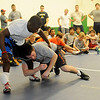 John Morrison demonstrates a single leg take down on Obe Blanc during the Enid Camp for Champs at Emerson Middle School Friday, August 2, 2013. Coleman Scott, Olympic Bronze Medalist and Oklahoma State University Wrestling Coach, directed the camp for wrestlers of all experience. (Staff Photo by BONNIE VCULEK)