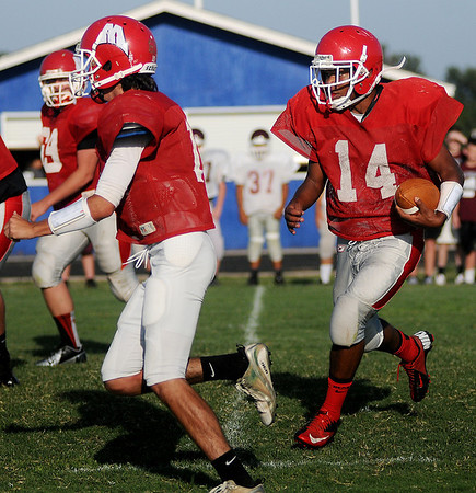 With a wall of blockers, Medford's Ryan Banks (right) races toward the end zone for a Cardinal touchdown during the DCLA scrimmage at Lamont Friday, August 30, 2013. (Staff Photo by BONNIE VCULEK)