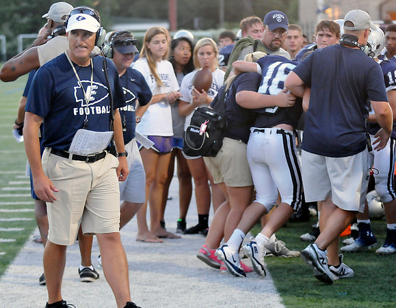 Enid head coach, Steve Chard (left), grimaces as Aaron Beagle (16) is helped to the bench after hurting his knee against during a scrimmage against Yukon Thursday at D. Bruce Selby Stadium. (Staff Photo by BILLY HEFTON)