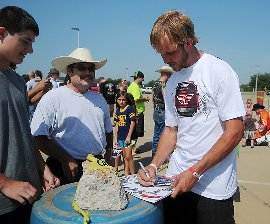 Enid native Brett Cue, a freestyling motor cross performer, autographs a poster for fans during the Cowboy Kenny Bartram Steel Rodeo Tour at the Greater Oklahoma Sportsman's Outdoor Expo at the Chisholm Trail Expo Center Saturday, August 24, 2013. Cue, who was injured doing a stunt Wednesday, described the tricks during the first performance at the event.(Staff Photo by BONNIE VCULEK)