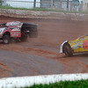 """Cars slide around turn one before No. 99 (right) blows an engine during the unofficial """"play day"""" event at Enid Speedway before the season-opener next week. Thirty-seven drivers participated in the event. (Staff Photo by BONNIE VCULEK)"""