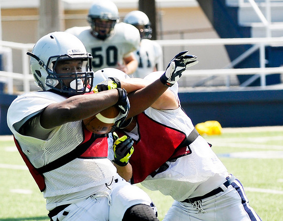 Alex Lofton is tackled after intercepting a pass during practice Friday. (Staff Photo by BILLY HEFTON)