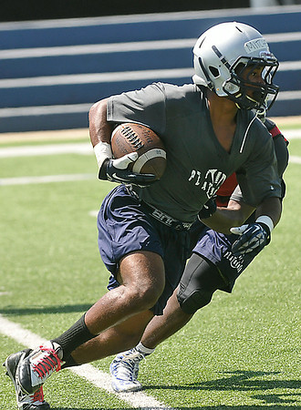 Enid's Raheem Mitchell runs the ball during the first day of practice at D. Selby Stadium Monday. (Staff Photo by BILLY HEFTON)