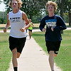 Enid's Garrett Wallace (left) and Gavin Lack during a warm-up run at Crosslin Park Monday. (Staff Photo by BILLY HEFTON)
