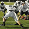 Enid head coach, Steve Chard, gets a close at the action as players take part in the Oklahoma drill early Friday morning. The team held a midnight practice on the first day that they were allowed to wear pads and have full contact. (Staff Photo by BILLY HEFTON)