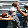 Enid High quarterbacks, Colten Troxel and Fred Lawrence, throw passes during the first day of practice at D. Selby Stadium Monday. (Staff Photo by BILLY HEFTON)