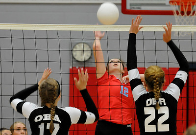 Chisholm's Jordan Rolfe hits the ball against OBA's Sage Kroeker and Katie Friesen Tuesday August 23, 2016 at Chisholm Middle School. (Billy Hefton / Enid News & Eagle)