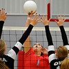 Chisholm's Cadee Fromm hits the ball against OBA's Elizabeth Price and Brooke Boydstun Tuesday August 23, 2016 at Chisholm Middle School. (Billy Hefton / Enid News & Eagle)