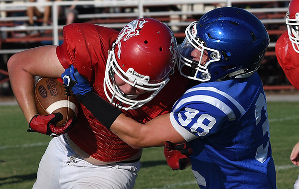 Kremlin-Hillsdale's Nathanal Snodgrass is hit by Lane Williams of Covington-Douglas during a scrimmage August 18, 2017 at Pioneer High School. (Billy Hefton / Enid News & Eagle)