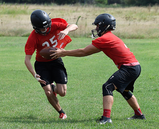 OBA's Jud Minx hands off to Landon Crismas during the first day of practice Monday August 7, 2017 at D. Bruce Selby Stadium. (Billy Hefton / Enid News & Eagle)