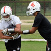 Brayden Keller takes a handoff from Angel Gonzales during the first day of practice Monday August 7, 2017 at medford High School. (Billy Hefton / Enid News & Eagle)