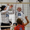 Enid's Catherine Cunningham with Gabi Cotarelo blocks the ball of Chisholm's Raylee Savage Tuesday August 21, 2018 at the NOC Mabee Center. (Billy Hefton / Enid News & Eagle)