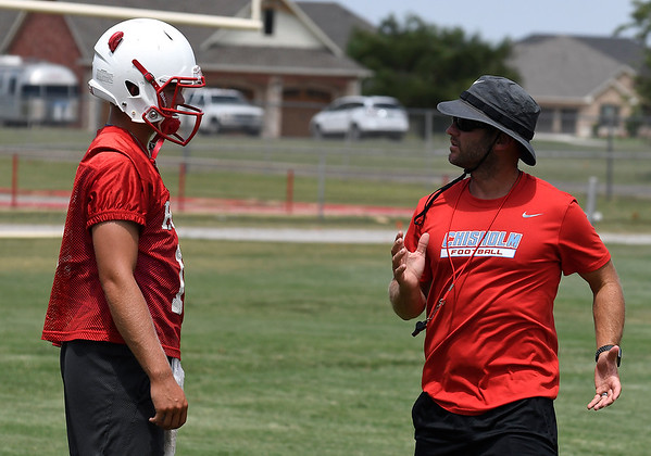 Chisholm head coach, Joey Reinart, talks to Braden Meek during the first day of practice Monday August 6, 2018 at Chisholm High School. (Billy Hefton / Enid News & Eagle)