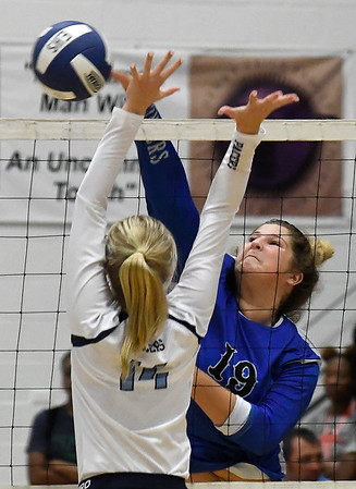 Stillwater's McKenzie Vilade hits the ball pass Enid's Hanna Brinley Tuesday August 28, 2018 at the NOC Mabee Center. (Billy Hefton / Enid News & Eagle)