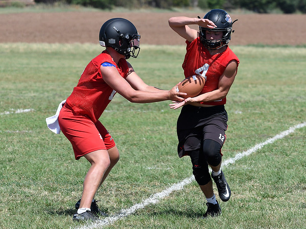 OBA's Traber Smithson tales a handoff from Baron Winter during the first day of practice Monday August 6, 2018 at Oklahoma Bible Academy. (Billy Hefton / Enid News & Eagle)