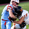 Chisholm's T.C. Smith is hit by Fairview's Zach Ramay August 31, 2018 at Chisholm High School. (Billy Hefton / Enid News & Eagle)