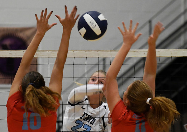 Enid's Catherine Cunningham hits the ball between Chisholm's Raylee Savage and Kaci Robinett Tuesday August 21, 2018 at the NOC Mabee Center. (Billy Hefton / Enid News & Eagle)
