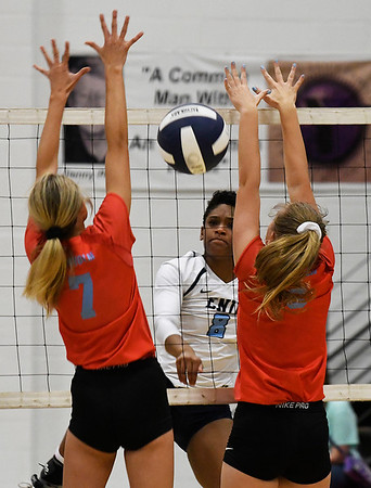 Enid's D'Sani Levy hits the ball between Chisholm's Cameron Madsen and Brooklyn Wilson Tuesday August 21, 2018 at the NOC Mabee Center. (Billy Hefton / Enid News & Eagle)