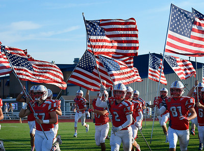 Chisholm High School players runs onto the field carrying American flag prior to their season opening game against Weatherford Friday, August 30, 2019. (Billy Hefton / Enid News & Eagle)