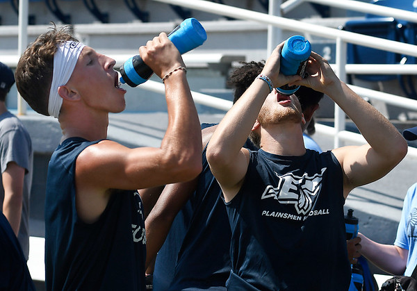 Reese Slater and Hayden Johnson take advantage of a water break during the first day of practice Monday, August 12, 2019 at D. Bruce Selby Stadium. (Billy Hefton / Enid News & Eagle)