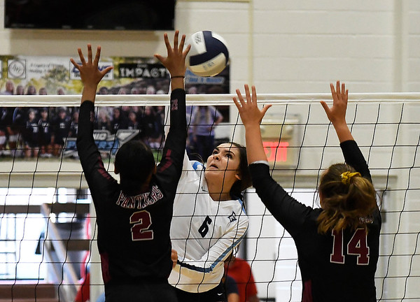 Enid's Jacqueline Camarena hits the ball against Putnam City North's Bria Sanders and Faith DeSouza Thursday, August 15, 2019 at the NOC Mabee Center. (Billy Hefton / Enid News & Eagle)