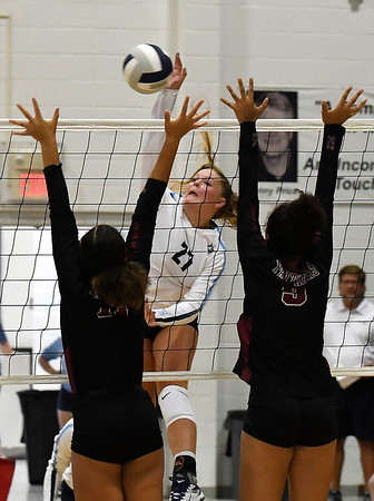 Enid's Catherine Cunningham hits the ball against Putnam City North's Mikayla Eagle and Reace Wright Thursday, August 15, 2019 at the NOC Mabee Center. (Billy Hefton / Enid News & Eagle)
