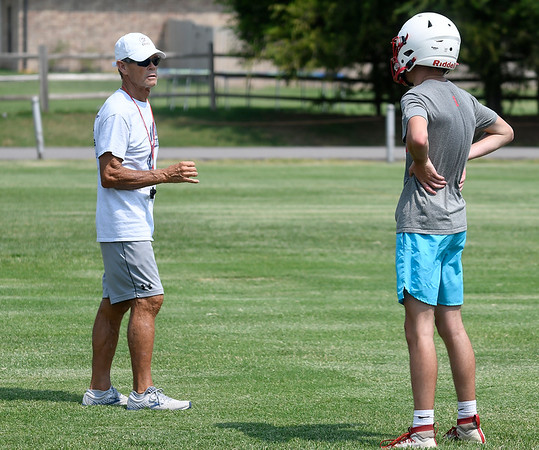 New Chisholm head coach, Lyle Welsh, talks to Bryce Patton throws during the first day of practice Monday, August 10, 2021 at Chisholm High School. (Billy Hefton / Enid News & Eagle)