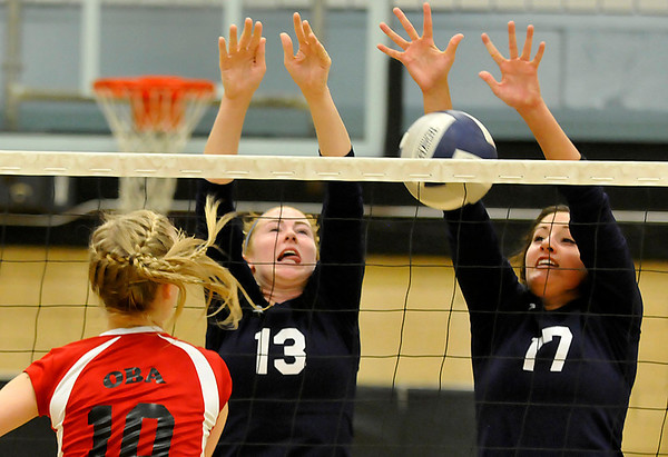Enid's Sarah Blakely and Grace Enmeier block the shot of OBA's Brooklyn Wiens Monday at Waller Middle School. (Staff Photo by BILLY HEFTON)