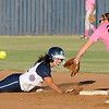 Courtney Chelf dives back into second base after hitting a RBI double against Edmond Memorial Monday at Pacer Field. (Staff Photo by BILLY HEFTON)