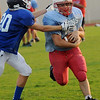 Chisholm linebacker, Justin Phrehm, eludes a Mooreland tackle after Phrehm intercepted a deep pass from the Bearcats' quarterback Thursday during the Longhorns' scrimmage at Chisholm High School. (Staff Photo by BONNIE VCULEK)