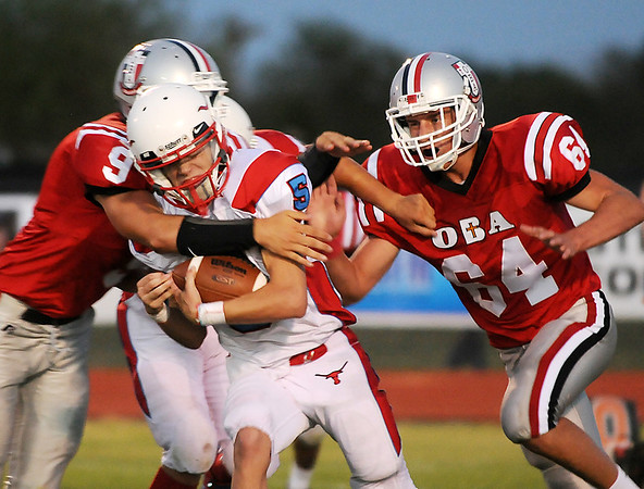 Oklahoma Bible Academy's Adan Eaton and Andrew Luskey combine to bring down  Chisholm quarterback, Tabor Charles, Thursday during the opening game of the season. (Staff Photo by BILLY HEFTON)