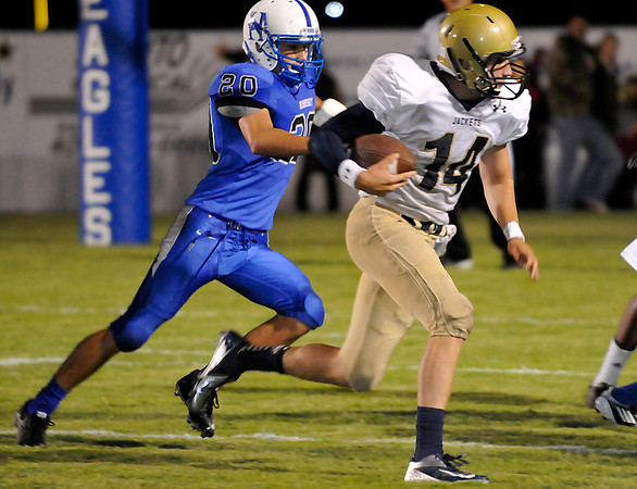 KIngfisher's Grant Newton is chased by Clay Moery of Hennessey during the first half Friday at Hennessey High School. (Staff Photo by BILLY HEFTON)