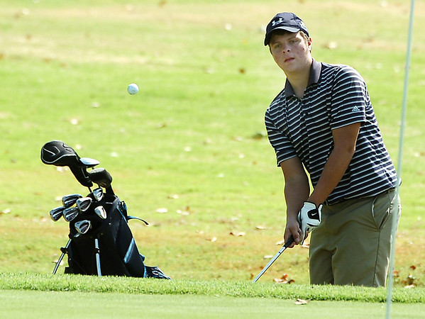 Chris Hayes chips onto the 18th green Monday at Oakwood Country Club during the Enid City Junior Golf Championship. (Staff Photo by BILLY HEFTON)