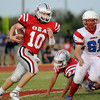 Oklahoma Bible Academy's Baylor Boyd runs pass Chisholm's Trevor Schober for a long gain during the opening game of the season Thursday. (Staff Photo by BILLY HEFTON)