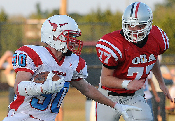 Chisholm's John Voss tries to run pass Nathan Meier of Oklahoma Bible Academy during the opening game of the season Thursday. (Staff Photo by BILLY HEFTON)
