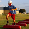 Members of the Chisholm High School football team go through drills in the early sun Tuesday on the first day of official practice for high school teams across the state. (Staff Photo by BILLY HEFTON)