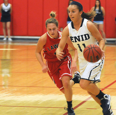 Enid's Abby Lee dribbles upcourt against Lawton's Sydnie Puziak Saturday at the NOC-Enid Mabee Center. (Staff Photo by BILLY HEFTON)